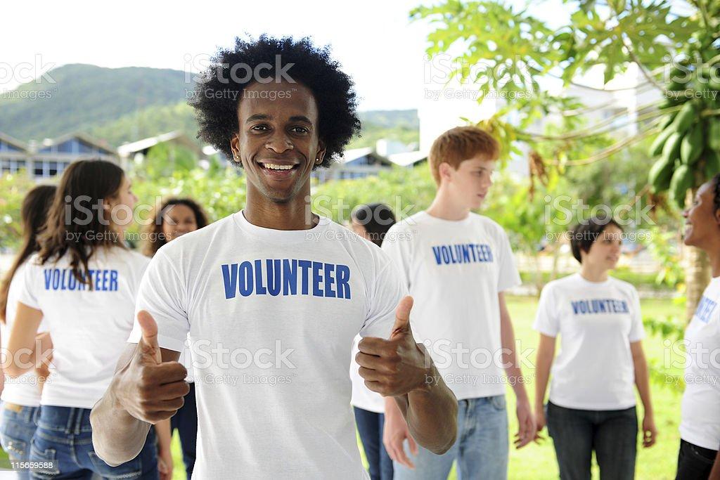 Voluntarios feliz african american man showing thumbs up señal - foto de stock