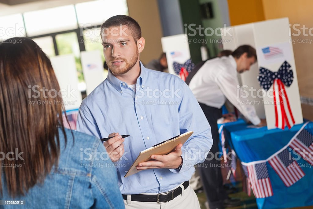 Happy volunteer asking exit poll questions at election voting center royalty-free stock photo