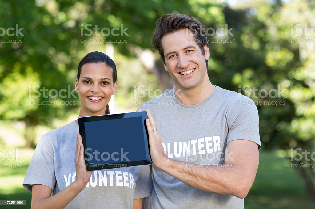 Happy volunteer couple holding tablet pc royalty-free stock photo
