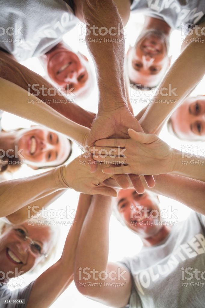 Happy volunteer family putting their hands together stock photo