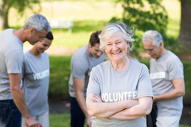feliz voluntário avó a sorrir para a câmara - voluntário imagens e fotografias de stock