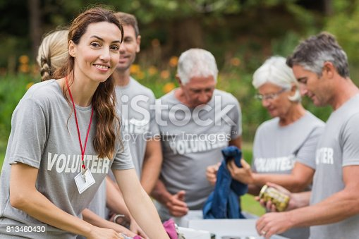 istock Happy volunteer looking at donation box 813460430
