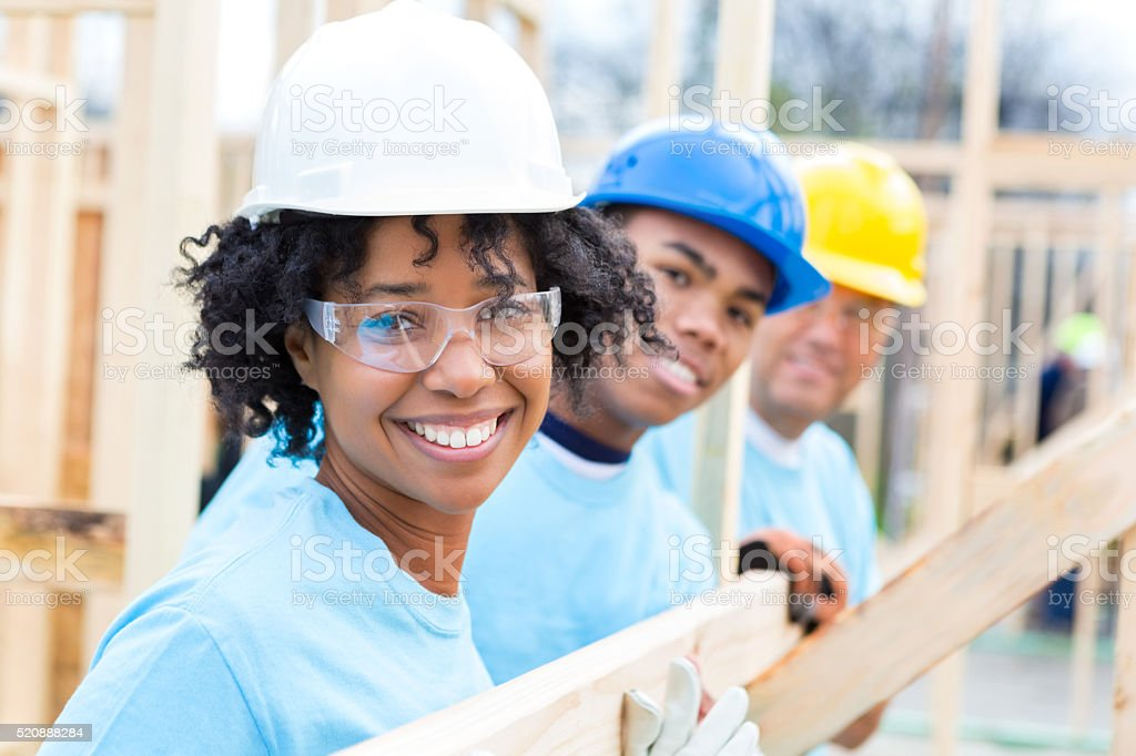 Happy volunteers at home construction site stock photo
