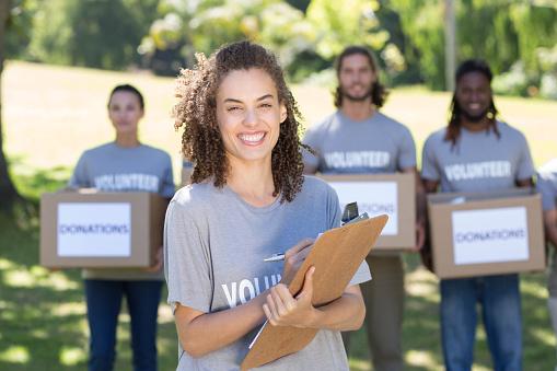 istock Happy volunteers in the park 472870850