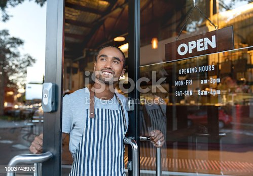 Portrait of a happy waiter opening on the doors at a cafe and smiling - small business concepts