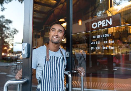 Happy Waiter Opening On The Doors At A Cafe — стоковые фотографии и другие картинки 20-29 лет