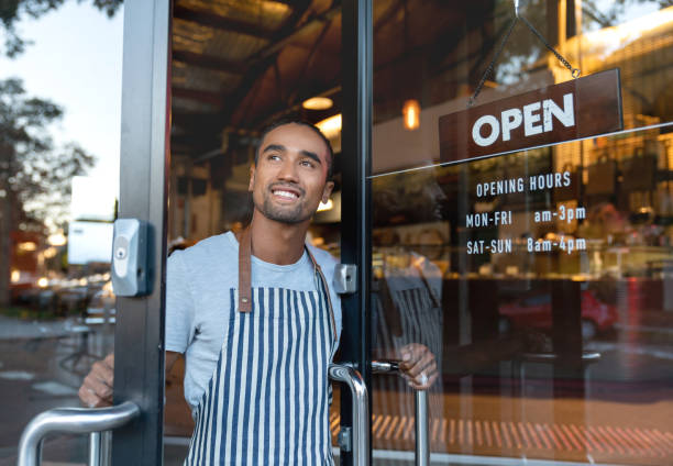 happy waiter opening on the doors at a cafe - owner stock pictures, royalty-free photos & images