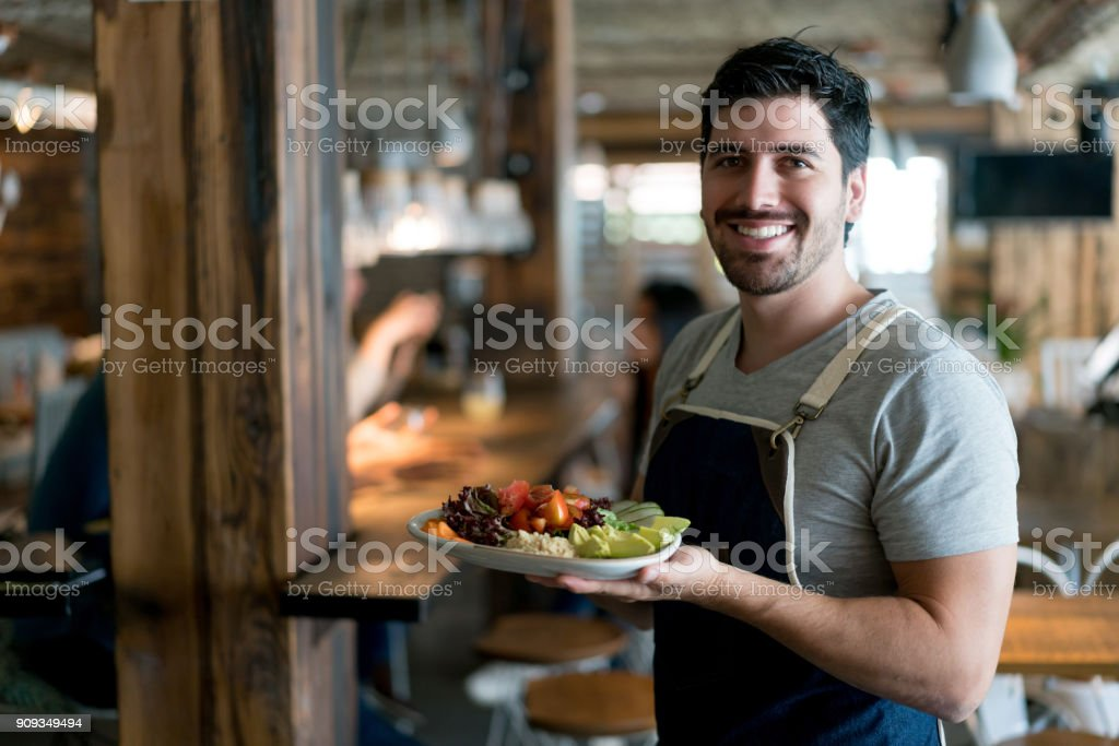Happy waiter serving food at a restaurant stock photo