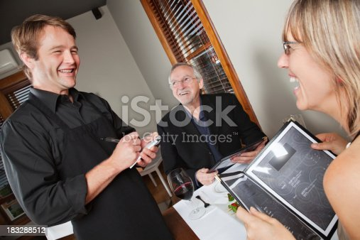 635812444 istock photo Happy Waiter Taking Order From Customers at Nice Restaurant 183288512