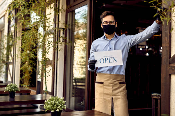 Happy waiter with protective face mask holding open sign while at picture id1227368755?b=1&k=6&m=1227368755&s=612x612&w=0&h=eav05fnx1zrkmdcc7n0j5kbosmkvnlopfmlhvhqluvi=