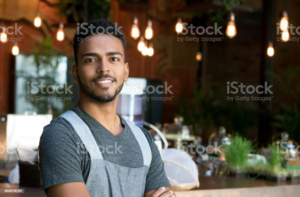 Happy waiter working at a restaurant stock photo