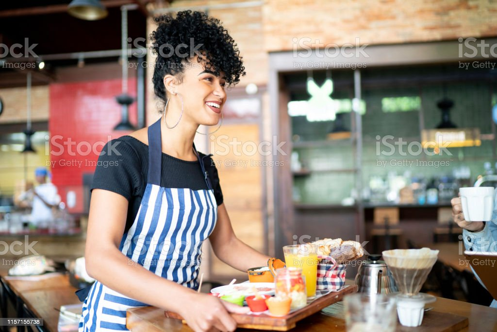 Happy waitress serving food to a group of friends in a cafeteria