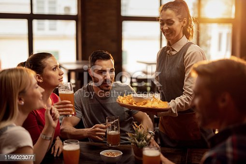 Group of happy friends drinking beer in a tavern while waitress is serving them nacho chips.