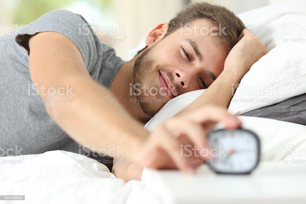 Happy wake up of a happy man stopping alarm clock stock photo
