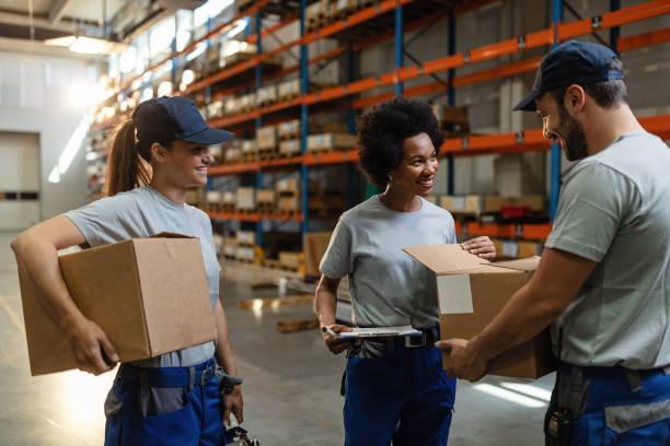 happy warehouse workers controleren kartonnen dozen voor de verzending. - warehouse worker stockfoto's en -beelden
