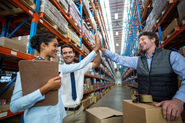 gelukkig magazijn werknemers geven hoge vijf - warehouse worker stockfoto's en -beelden
