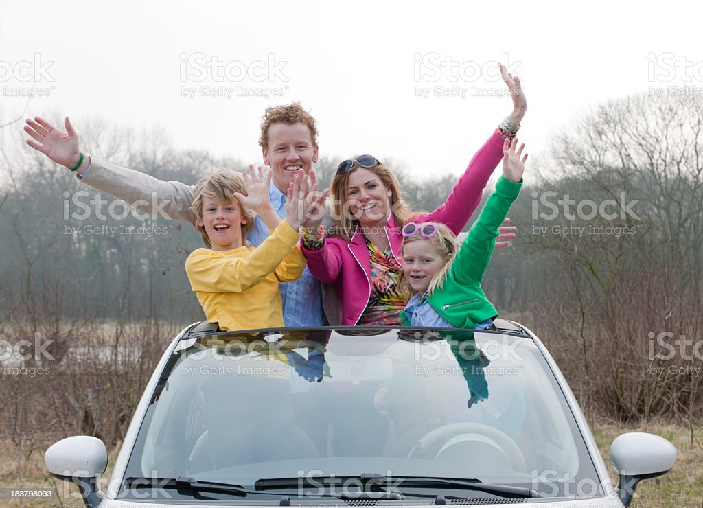 happy waving family standing in car XXXL image stock photo