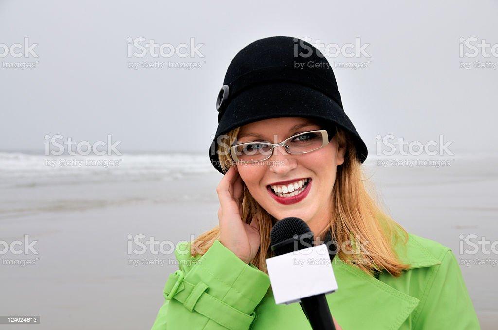 Feliz clima repórter em pé na praia - foto de acervo