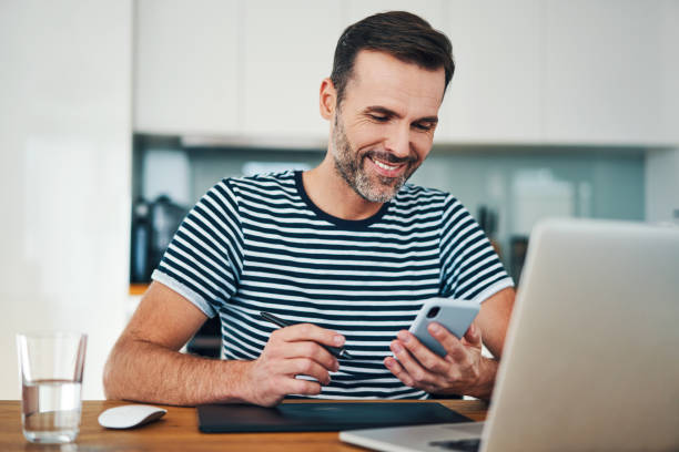 Happy web designer looking at smartphone while taking break from working in home office stock photo