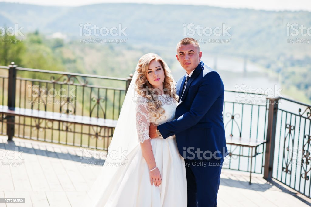 Happy wedding couple in love at observation deck on sunny day. royalty-free stock photo