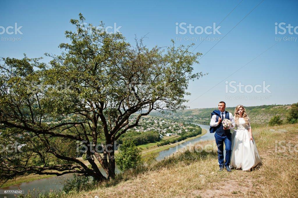 Happy wedding couple in love near trees on sunny day. royalty-free stock photo