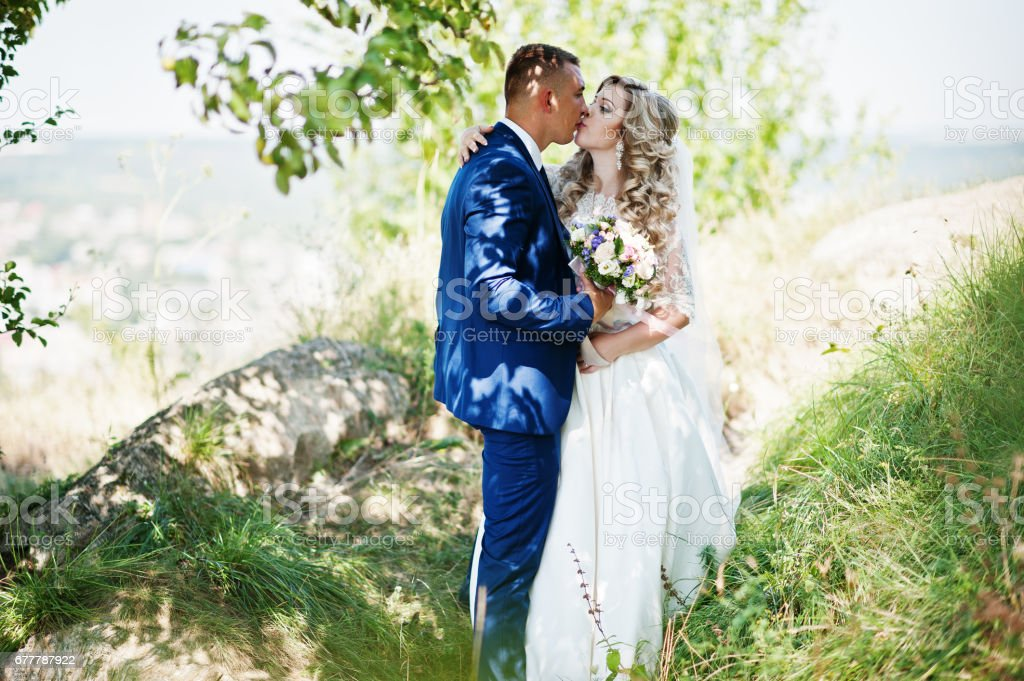 Happy wedding couple in love on sunny day stay near trees. royalty-free stock photo
