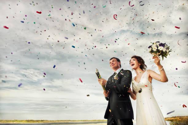 glückliches hochzeitspaar startet konfetti feuerwerk - outdoor braut duschen stock-fotos und bilder