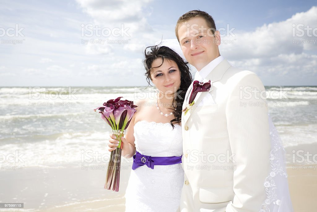 happy wedding couple portrait high key along seashore royalty-free stock photo