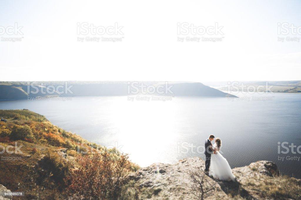 Happy wedding couple staying over beautiful landscape stock photo