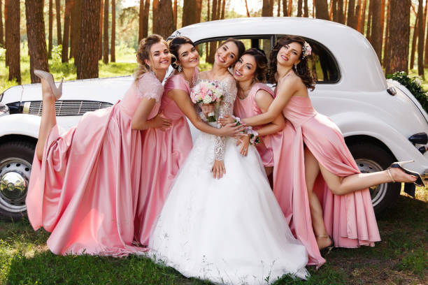 Happy wedding day. Beautiful bride and bridesmaids in pink dresses embracing with smile outdoors stock photo