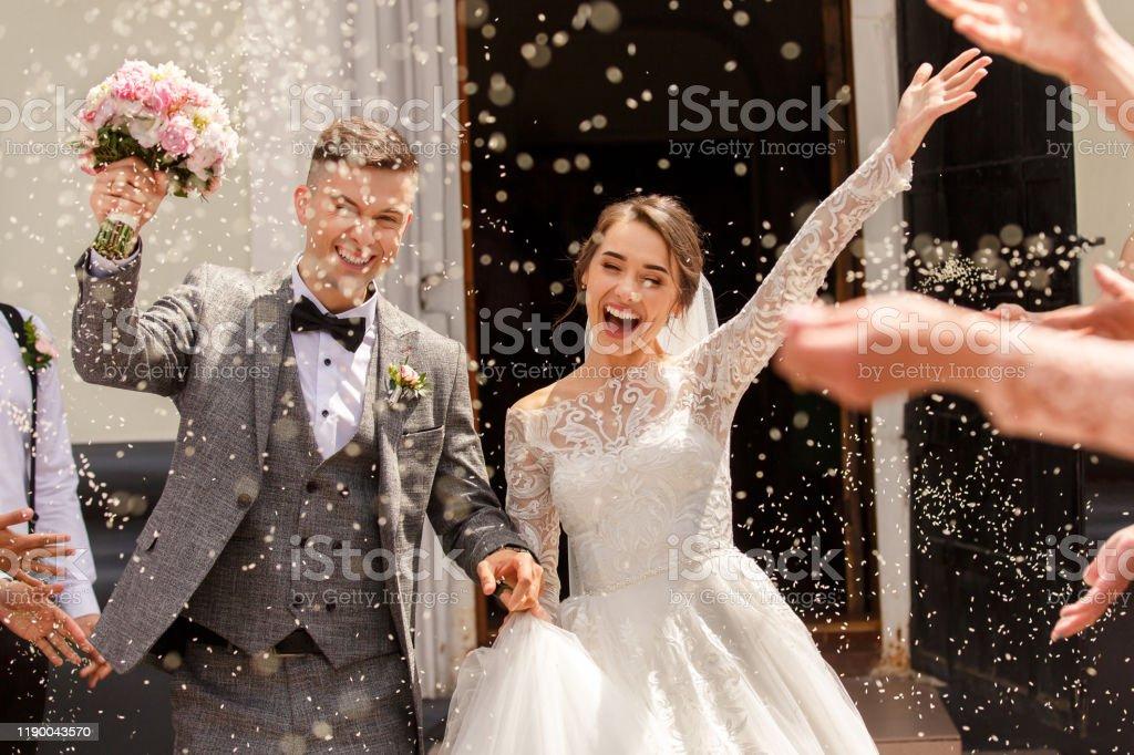 Gelukkige bruiloft fotografie van bruid en bruidegom op huwelijksceremonie. Bruiloft traditie bestrooit met rijst en graan - Royalty-free Begrippen Stockfoto