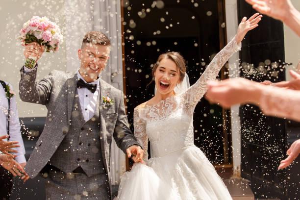 結婚式で新郎新婦の幸せな結婚式の写真。米と穀物を振りかけた結婚式の伝統 - 結婚式 ストックフォトと画像