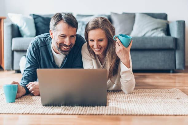 feliz fin de semana en casa - happy couple sharing a cup of coffee fotografías e imágenes de stock