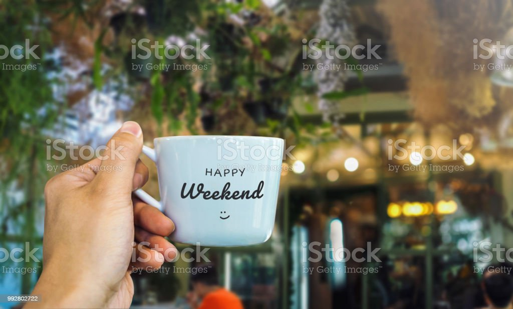Happy weekend text on mug with cafe view stock photo