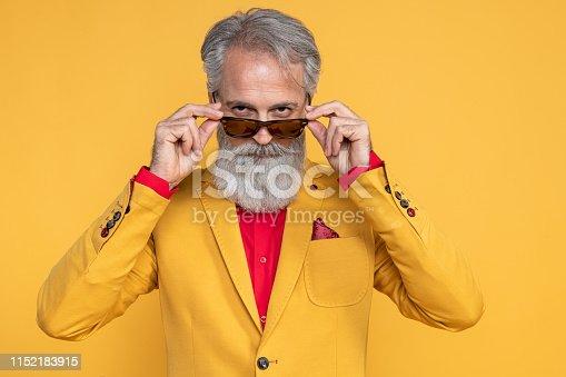 istock Happy well dressed gentleman having photoshooting in studio 1152183915