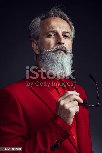 Portrait of senior man wearing red jacket on dark background. Styled, well dressed man.