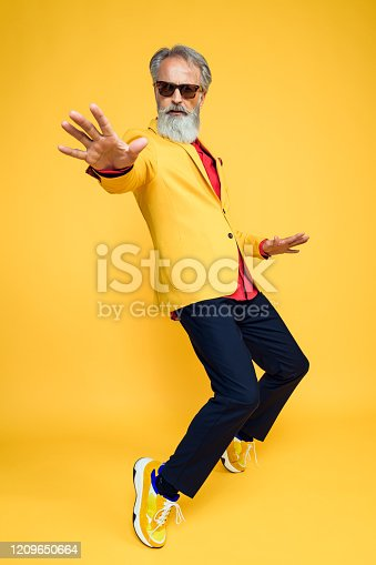 Portrait of senior man wearing yellow jacket on yellow background. Styled, well dressed man.