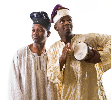 A brightly lit studio shot of two ethnic music performers in traditional dress clothing; isolated on a white background.