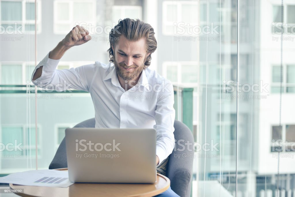 Happy western businessman using a laptop in living room stock photo