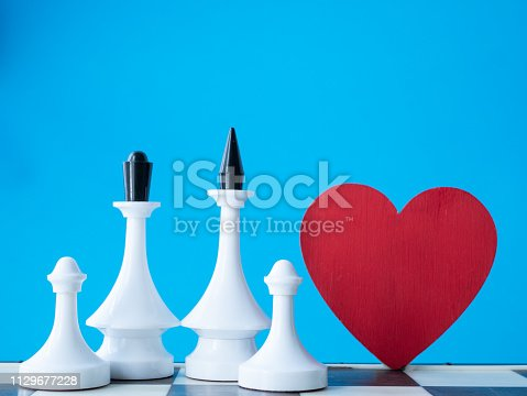 istock happy white caucasian family concept. chessman king, queen and two pawns near red heart with blue background 1129677228