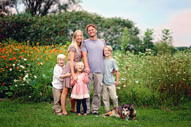 Happy Wholesome Caucasian Family and Dog Smiling and Posing by Flowers stock photo