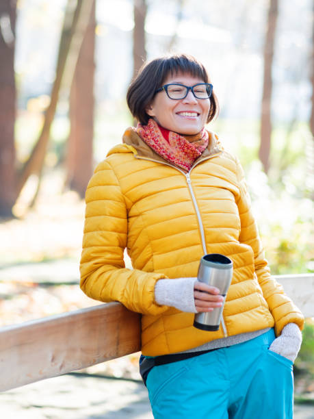 Happy wide smiling women in bright yellow jacket is holding thermos mug. Hot tea or other beverage on cool autumn day. stock photo