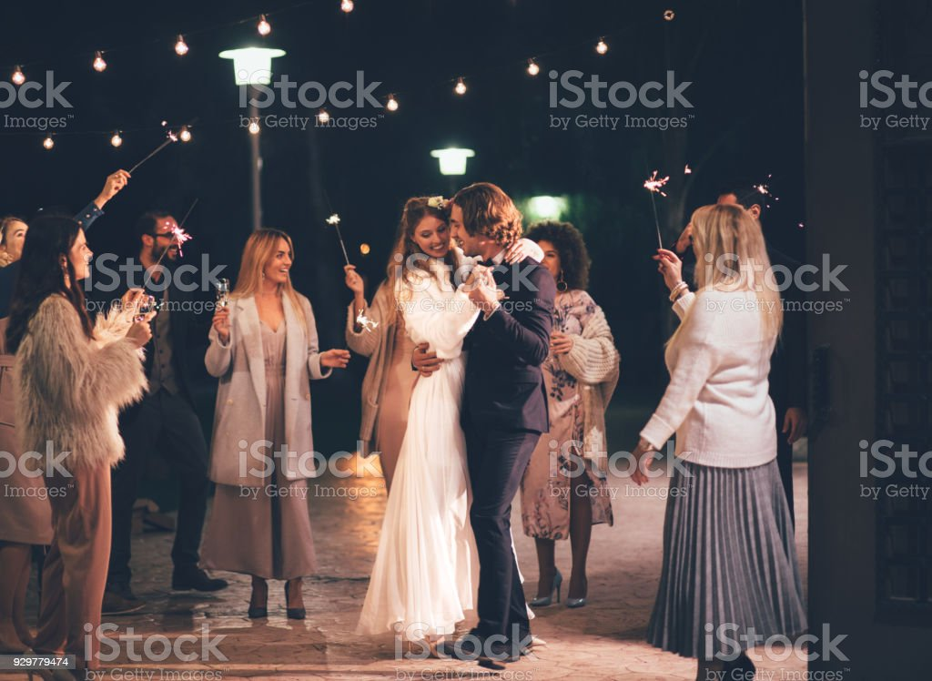 Happy wife and groom dancing at night outdoors wedding reception stock photo