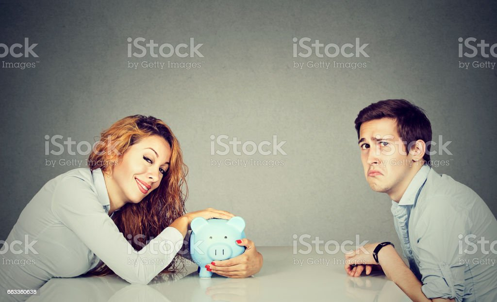 Happy wife with piggy bank sitting across the table from sad desperate ex husband stock photo