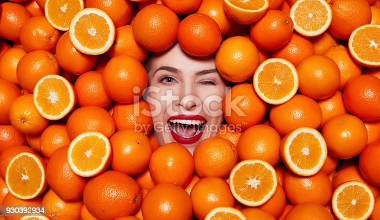 portrait of happy woman winking, surrounded by oranges, expressing positivity.