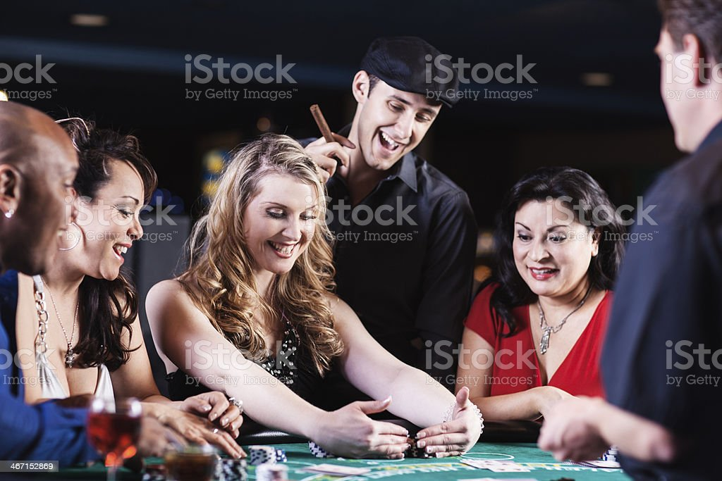 Happy winner among diverse people at the blackjack table royalty-free stock photo