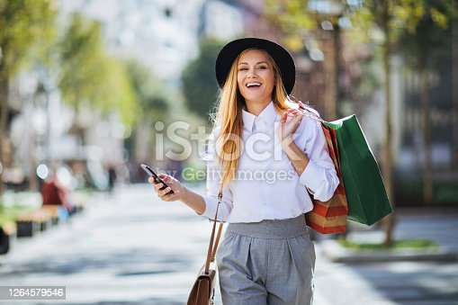 Young blond woman walking outdoors after shopping