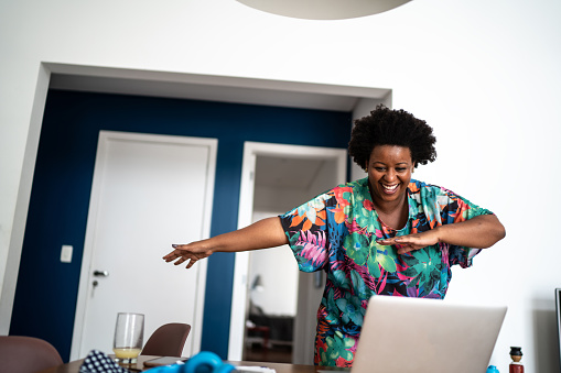 Happy woamn dancing at home in front of laptop during a virtual happy hour