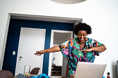 istock Happy woamn dancing at home in front of laptop during a virtual happy hour 1280569541