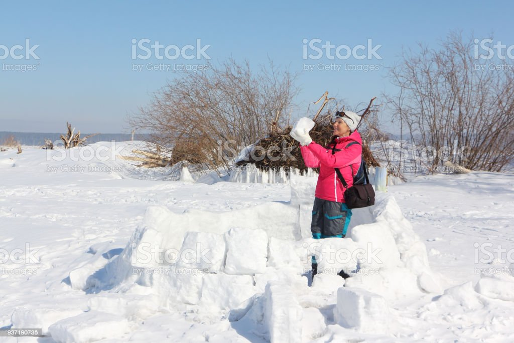 Happy Woman A Red Jacket Building An Igloo On A Snow Glade